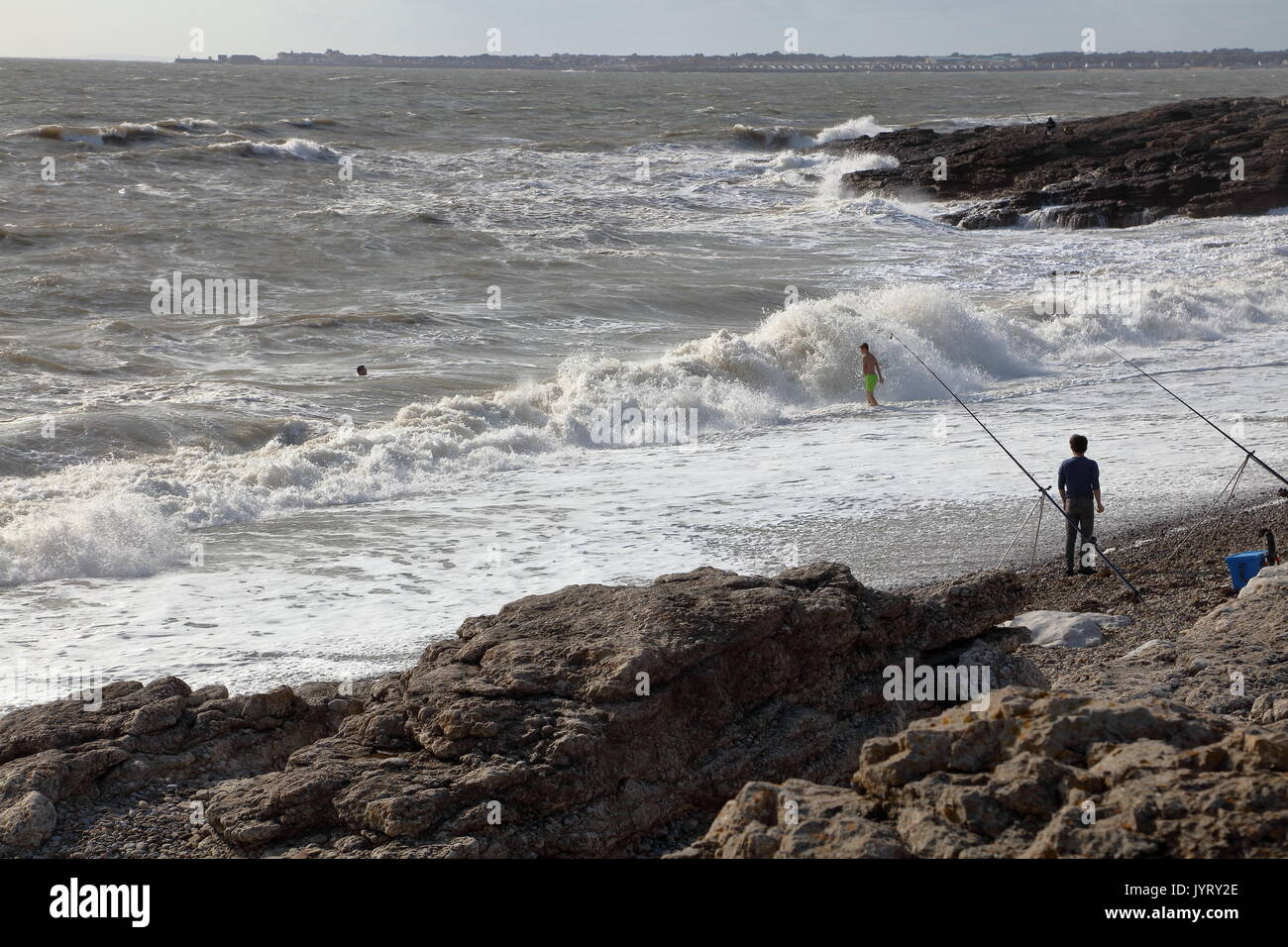 Anglers with rods fishing on a beach and swimmers riding the waves as they roll in into the beach on a sunny day. - Stock Image