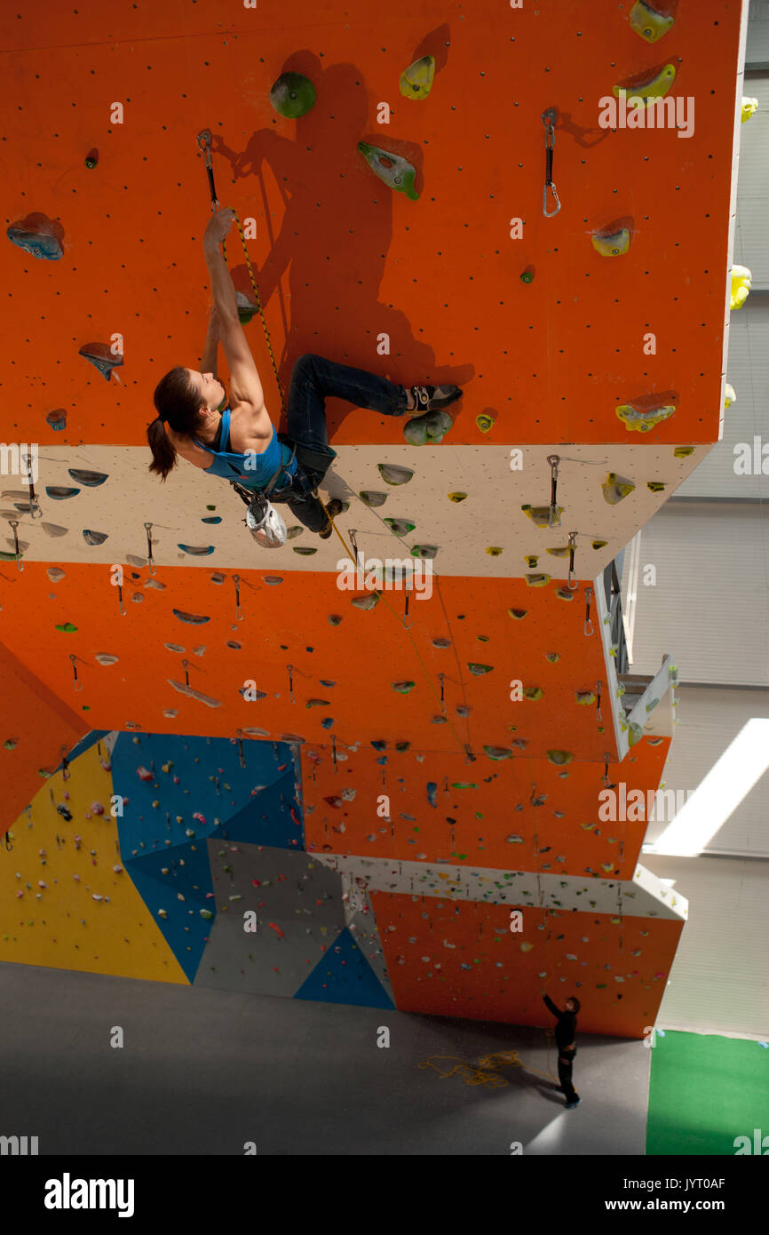 Young woman climbing indoor wall. Europe. - Stock Image