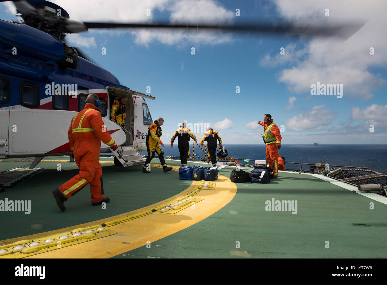 Bristow Helicopter, landing on a north sea oil and gas platform,  while passengers disembark. credit: LEE RAMSDEN Stock Photo