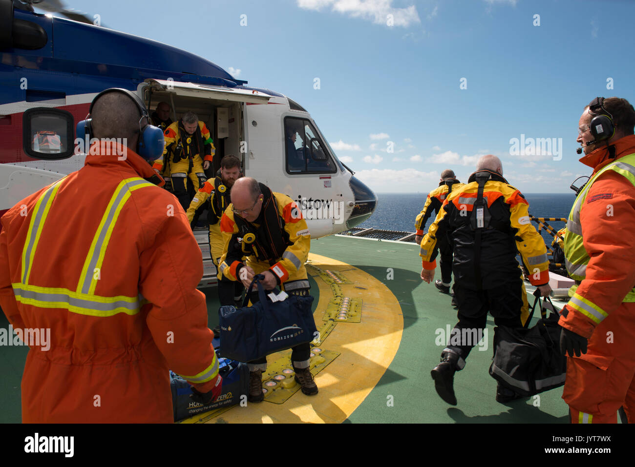 Bristow Helicopter, landing on a north sea oil and gas platform,  while passengers disembark. credit: LEE RAMSDEN / ALAMY - Stock Image