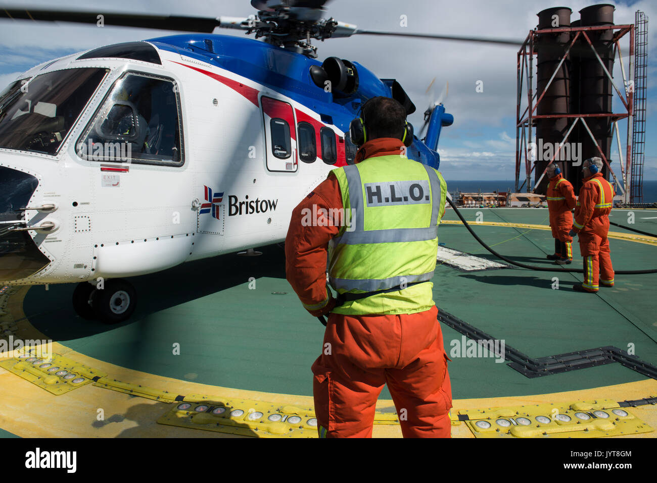 Bristow Helicopter, landing on a north sea oil and gas platform. Helideck team refuelling, credit: LEE RAMSDEN / ALAMY - Stock Image
