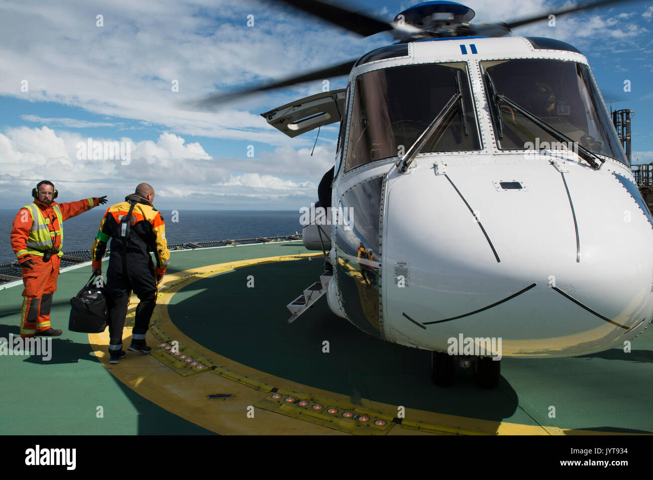 Bristow Helicopter, landing on a north sea oil and gas platform. while passengers disembark. credit: LEE RAMSDEN / ALAMY - Stock Image