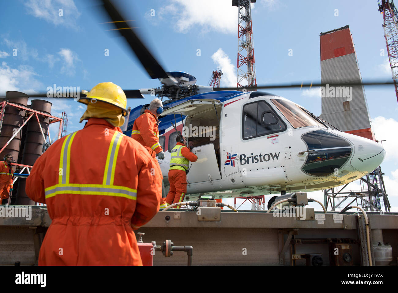 Bristow Helicopter, landing on a north sea oil and gas platform. Helideck team, controlling while passengers disembark. credit: LEE RAMSDEN / ALAMY - Stock Image