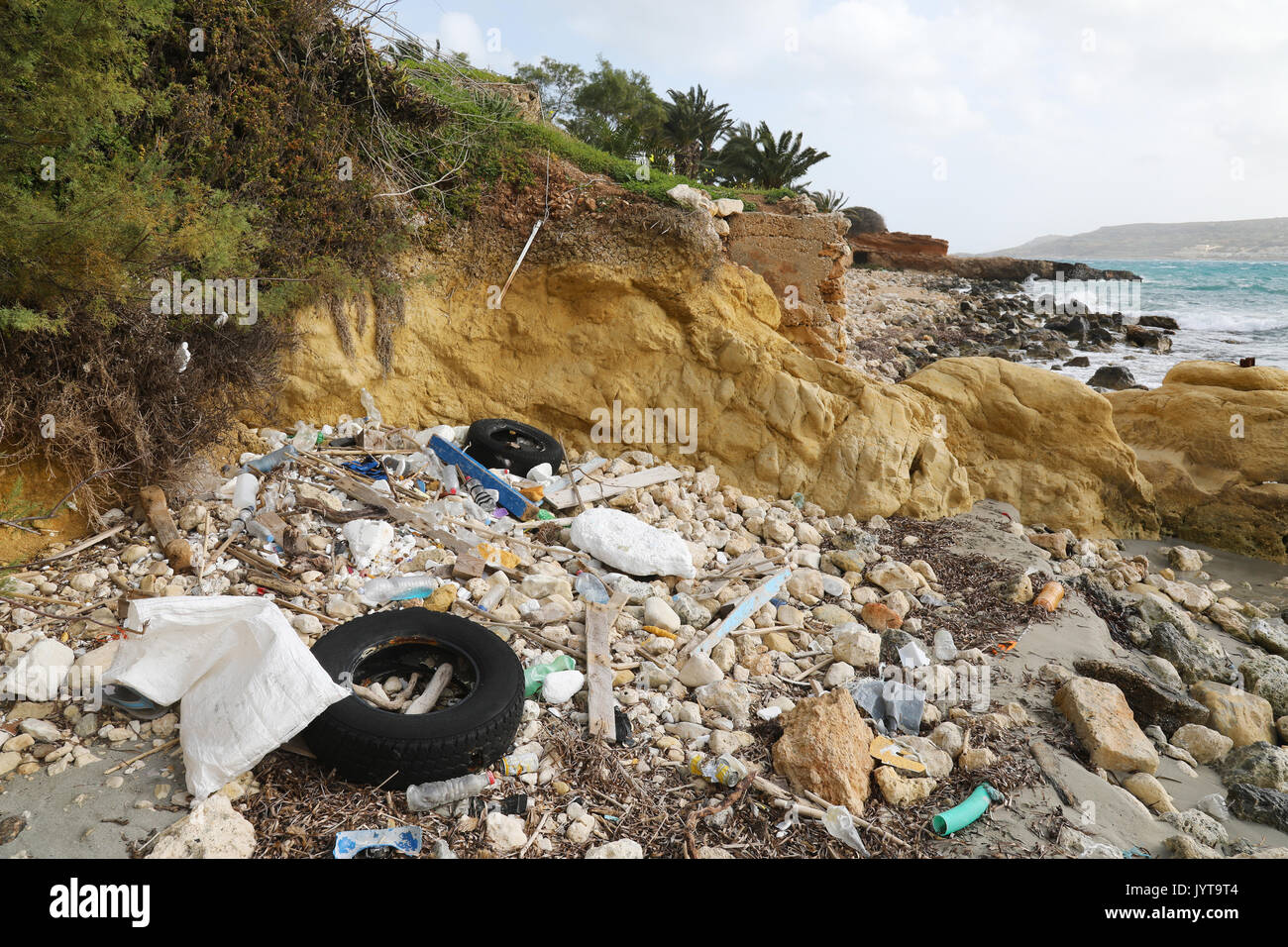 Litter and discarded old tires on the sea shore in Malta - Stock Image