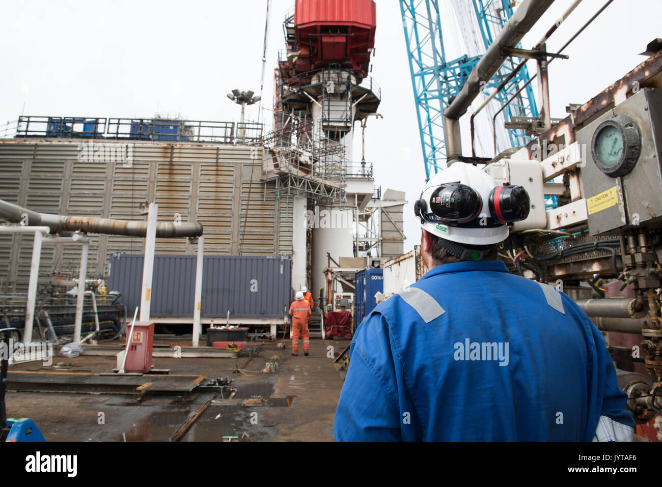 Oil and gas worker, overseeing a lifting operation on a North Sea oil and gas rig. credit: LEE RAMSDEN / ALAMY - Stock Image