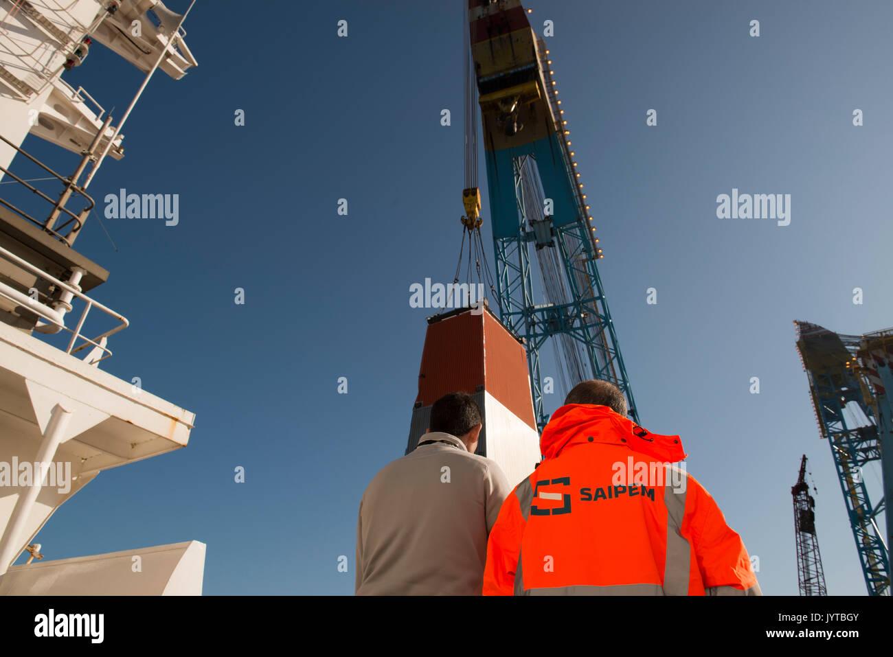 Saipem worker wearing hi-viz coat, watching the removal of a drilling derrick. credit: LEE RAMSDEN / ALAMY Stock Photo