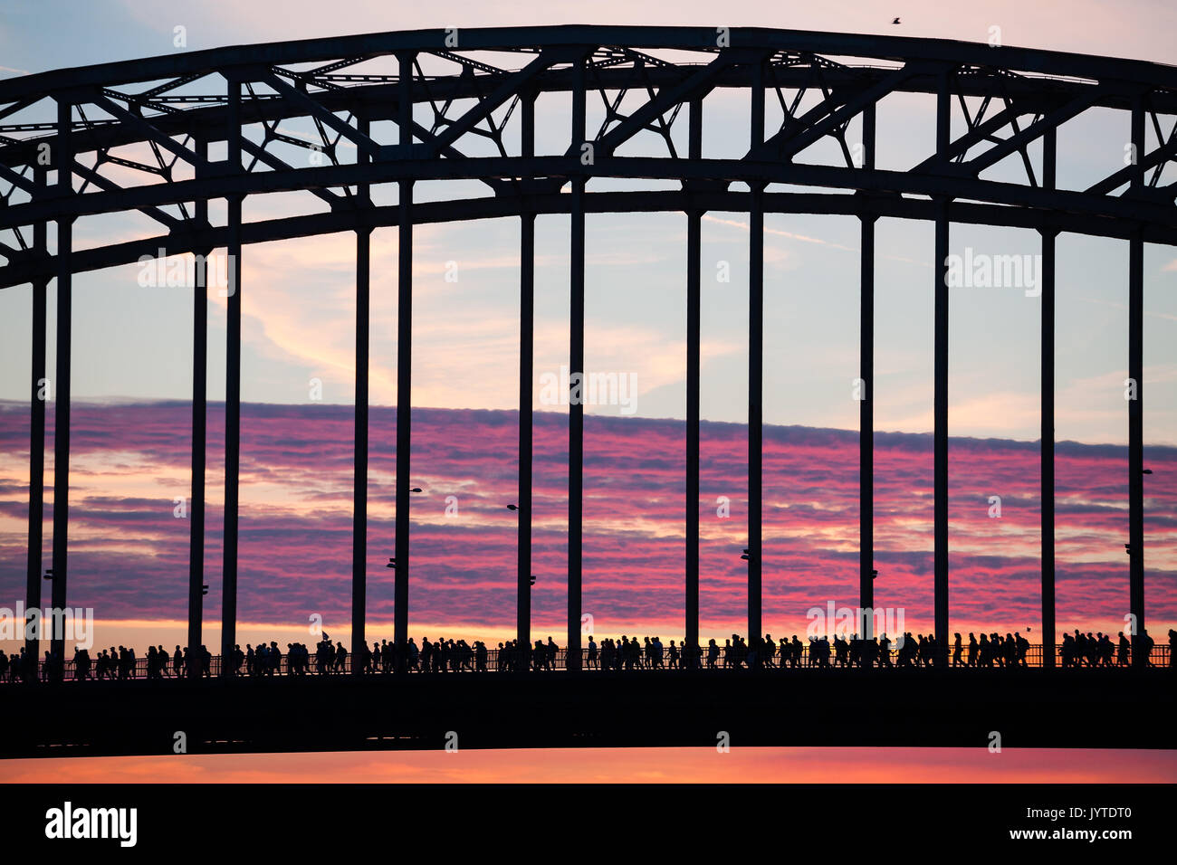 Participants of the 101st annual International Four Days Marches cross the Waalbrug in Nijmegen at sunrise - Stock Image