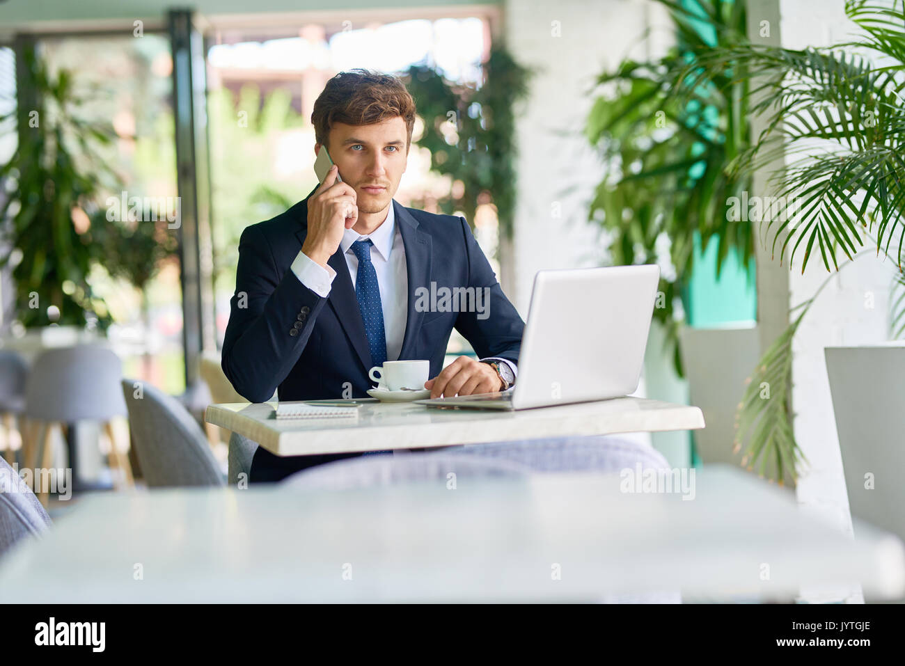Contemporary Businessman Working in Cafe - Stock Image