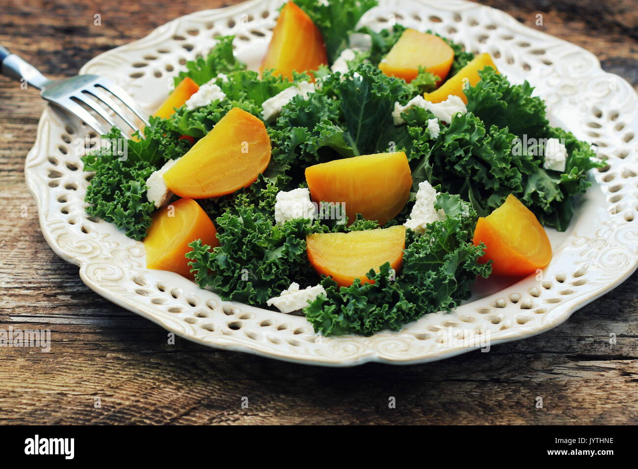 Healthy gollden beet salad with fresh kale lettuce, nuts, feta cheese on wooden background - Stock Image