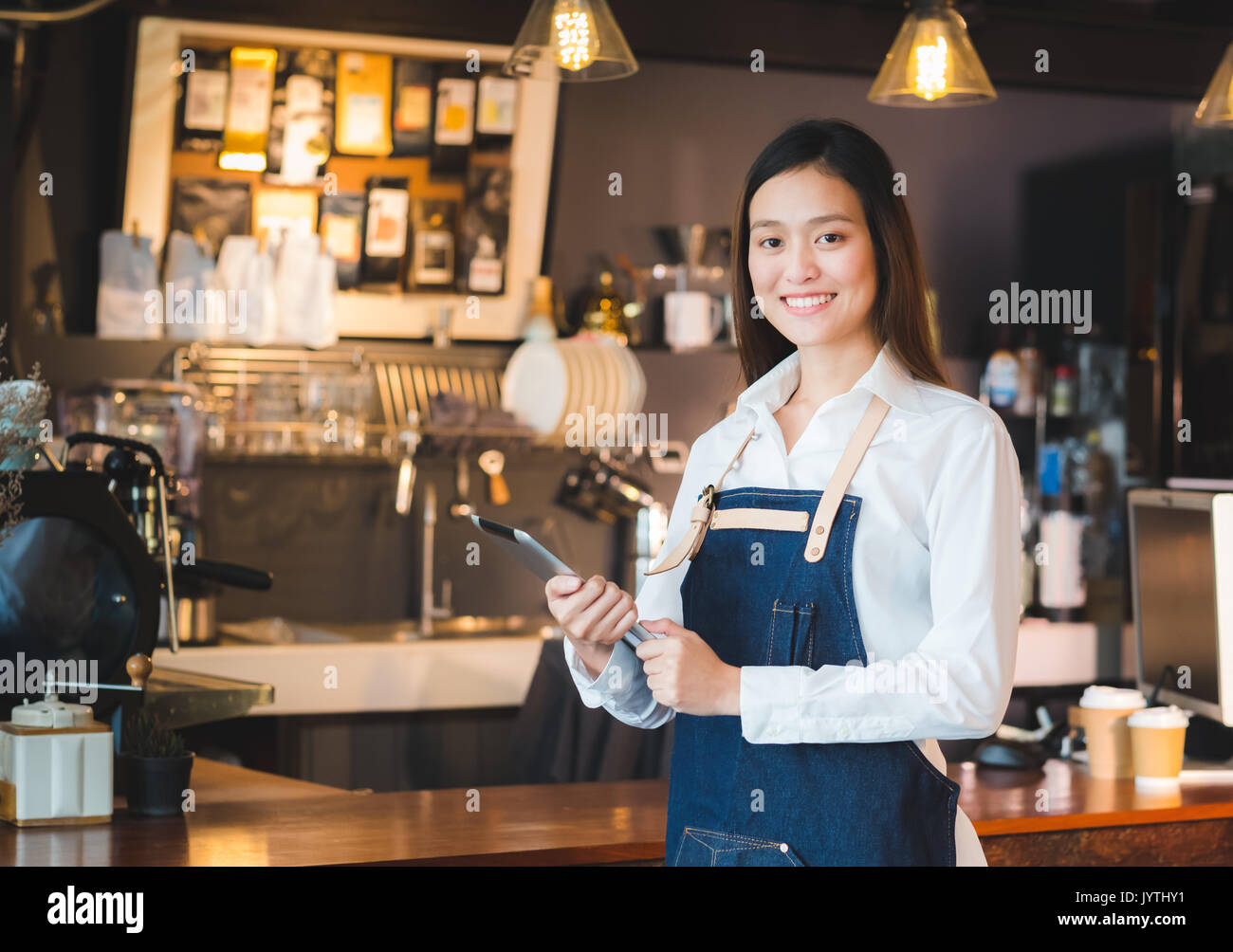 Asian female barista wear jean apron hold tablet computer coffee menu at counter bar with smile face,cafe service concept. - Stock Image