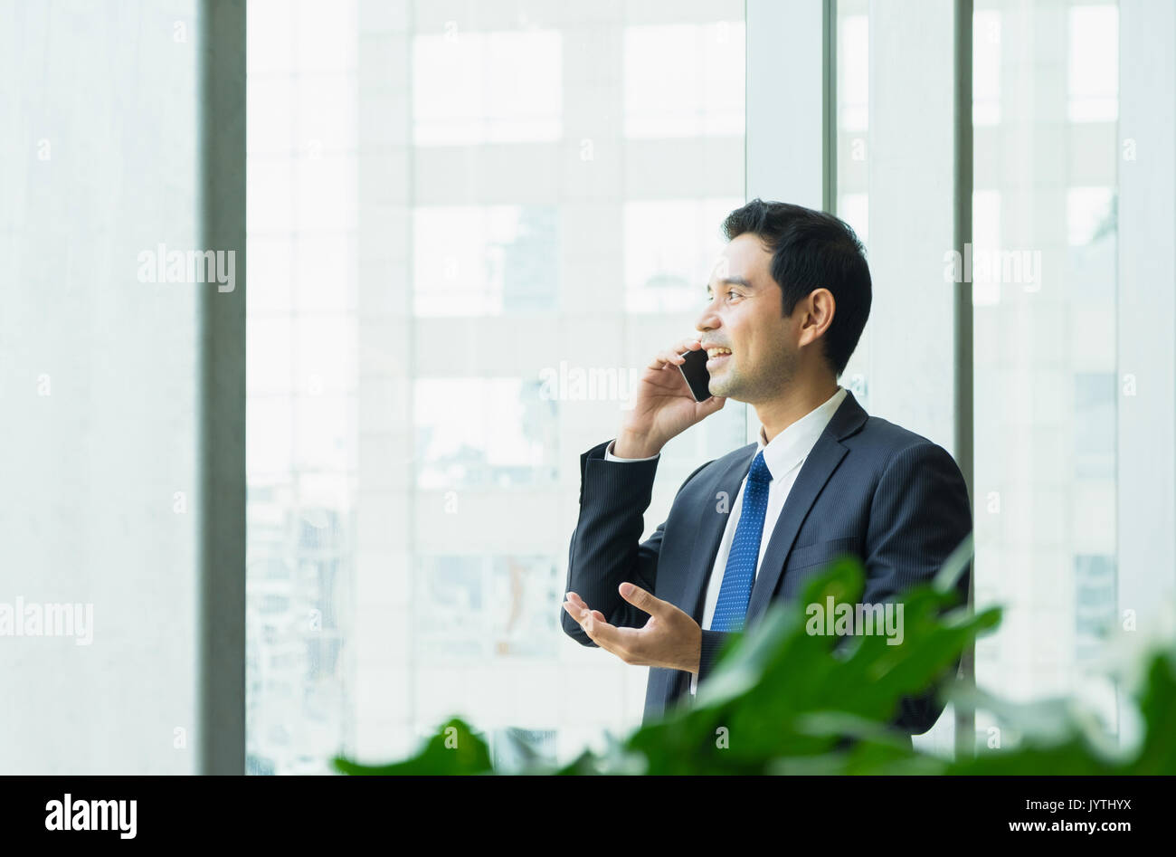 Businessman using mobile phone near office window at receptions area,Negotiation concept. - Stock Image