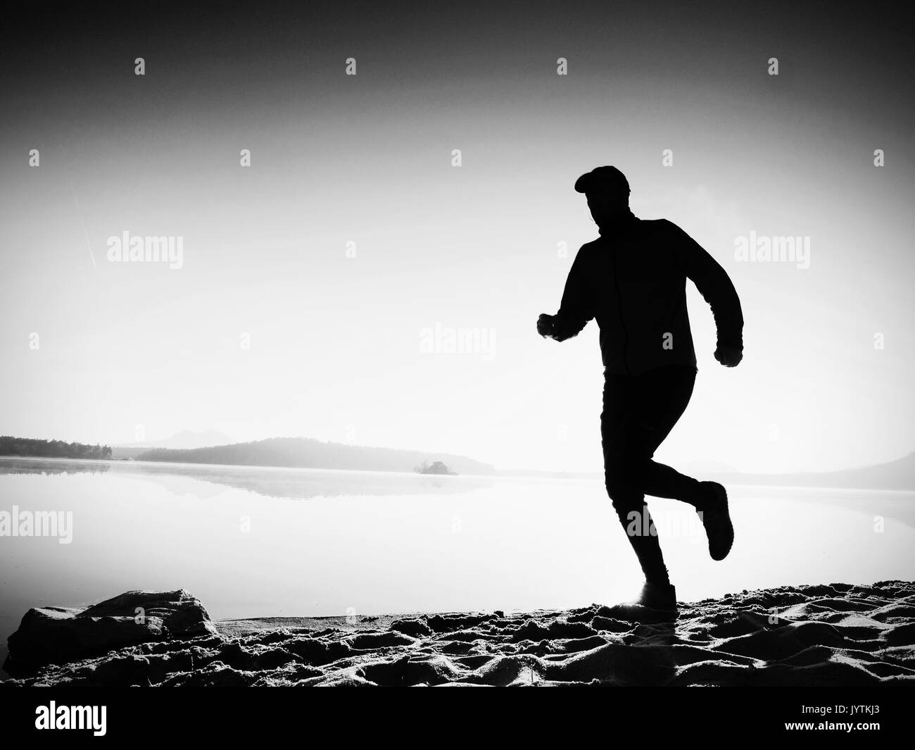Slim young fitness man runner on beach, tropical trail runner.  Cheerful sportsman run on beach among the water, personal  event. Sunrise hot sun at h - Stock Image