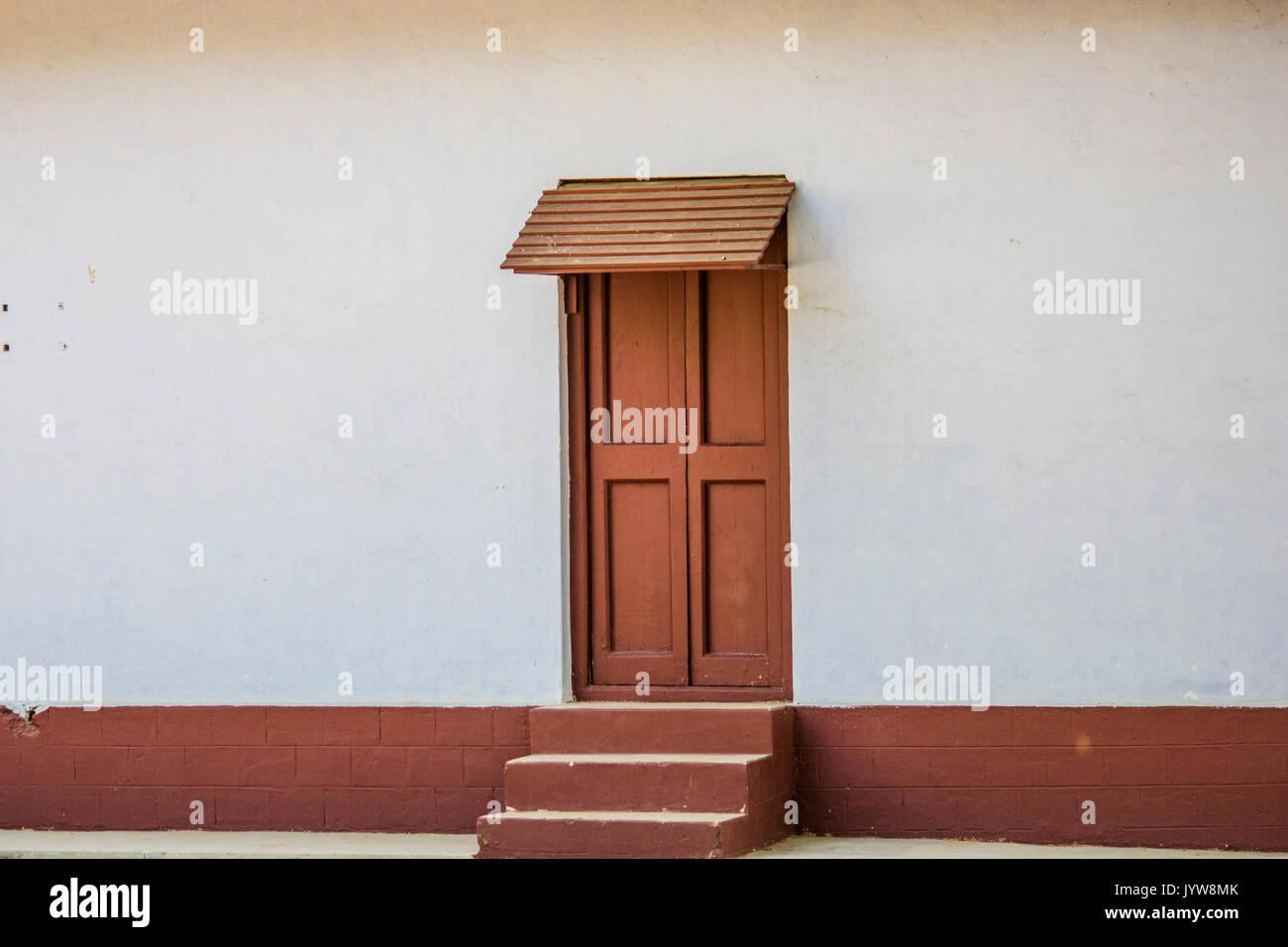 dark red closed wooden door with steps - Stock Image