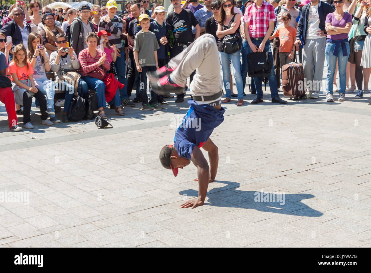 PARIS, FRANCE -  APRIL 25:B-boy doing some breakdance moves in front a street crowd, at Arch of Triumph on april 25, 2013 in Paris. - Stock Image