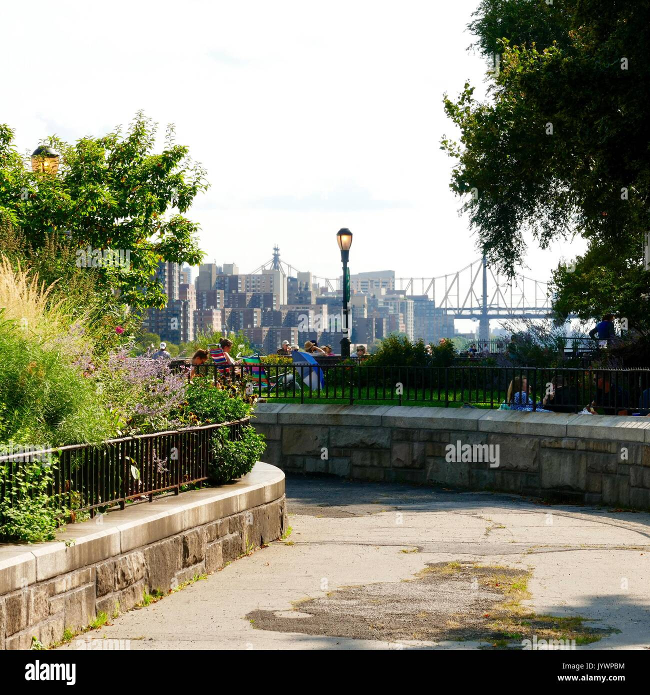 People relaxing on the grass at Carl Schurz Park on a Saturday afternoon. Upper Eastside, Manhattan, New York, New York, USA. - Stock Image
