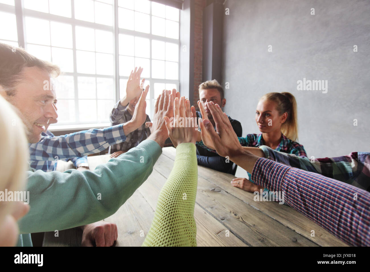 Modern business meeting concept, people in casual clothes sitting around wooden table giving high five - Stock Image