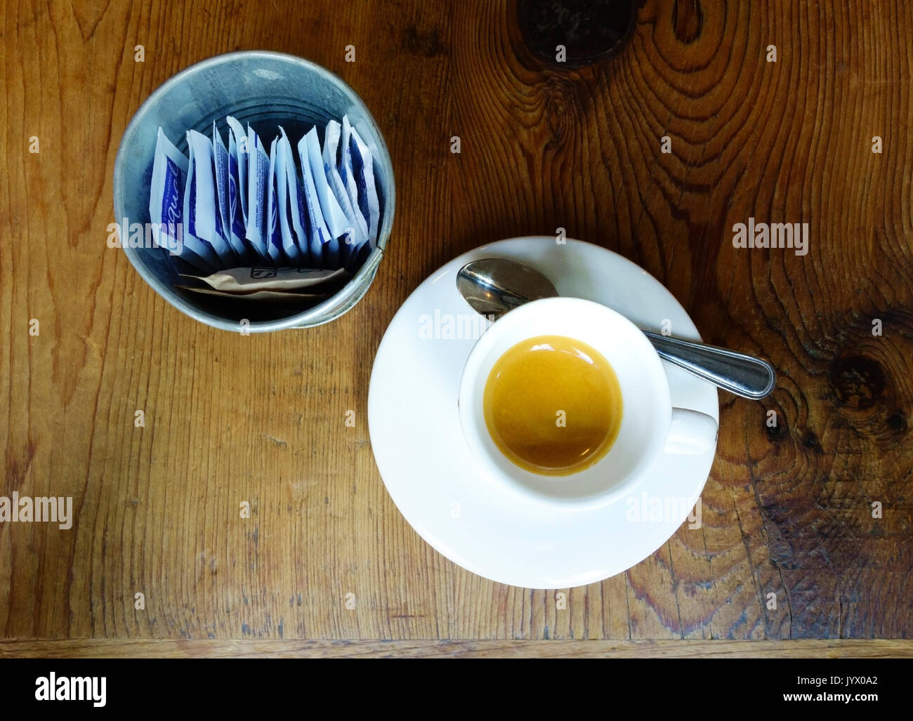 A cup of espresso next to a container holding packets of Equal, a sugar substitute, and two brown sugar packets on a wooden counter - Stock Image