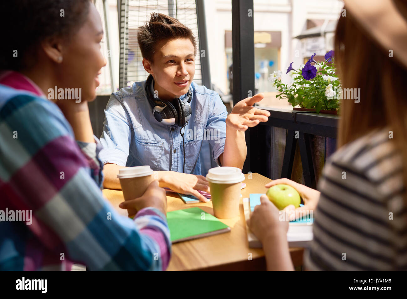 Asian Student Talking to Friends in Cafe - Stock Image