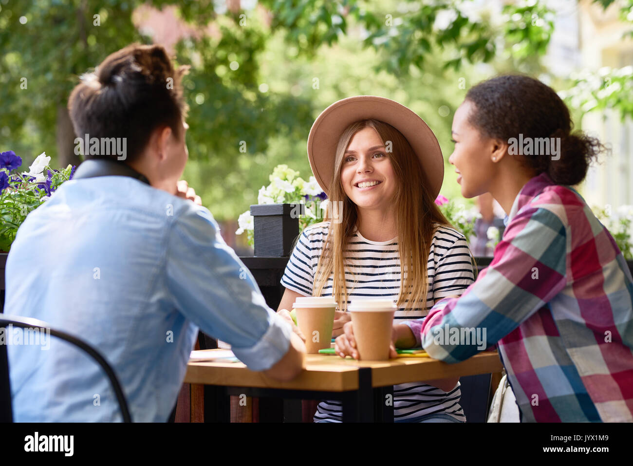 Students Chatting at Lunch in Cafe Outdoors - Stock Image