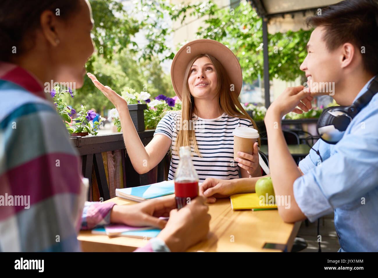 Young People Chatting in Cafe - Stock Image