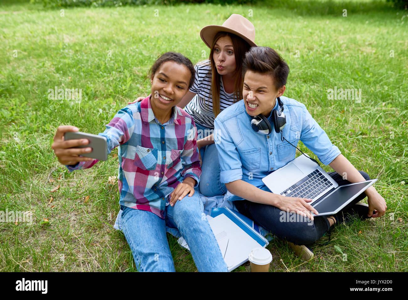Grimacing Teenagers Taking Selfie in Park - Stock Image