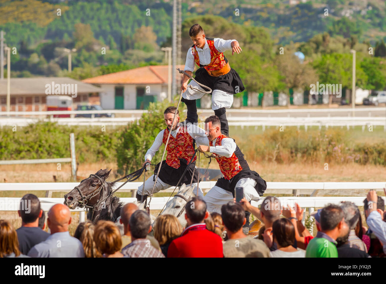 Sardinia horse riding, a three man team perform a traditional horse riding feat at the Ippodrome race track during the Cavalcata festival in Sassari. - Stock Image