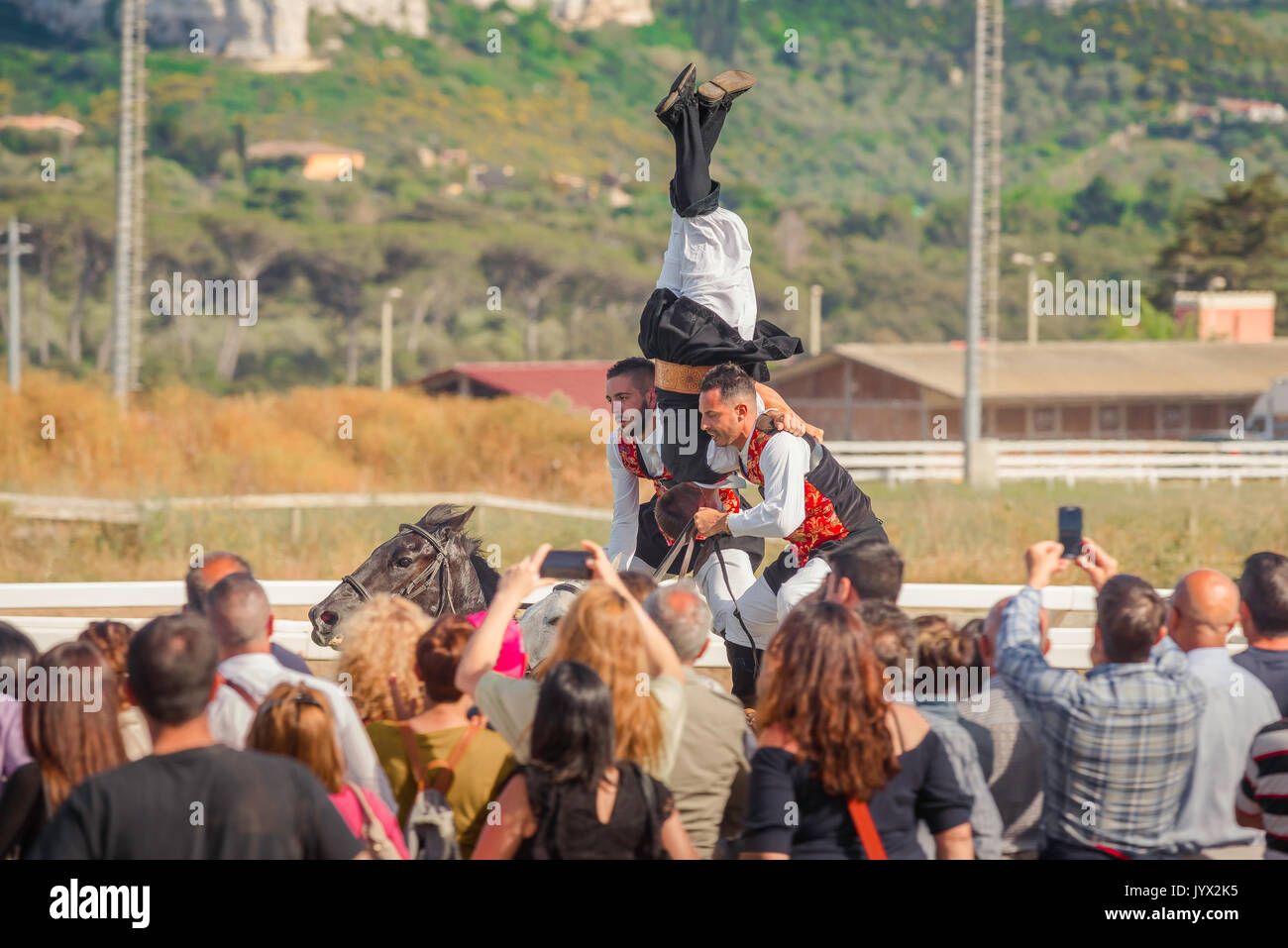 Festival Sardinia, a three man team perform a traditional horse riding feat at the Ippodrome race track during the Cavalcata festival in Sassari. - Stock Image