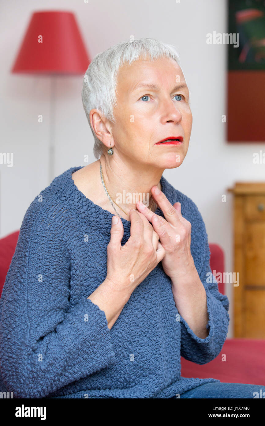 Senior woman touching her thyroid gland - Stock Image