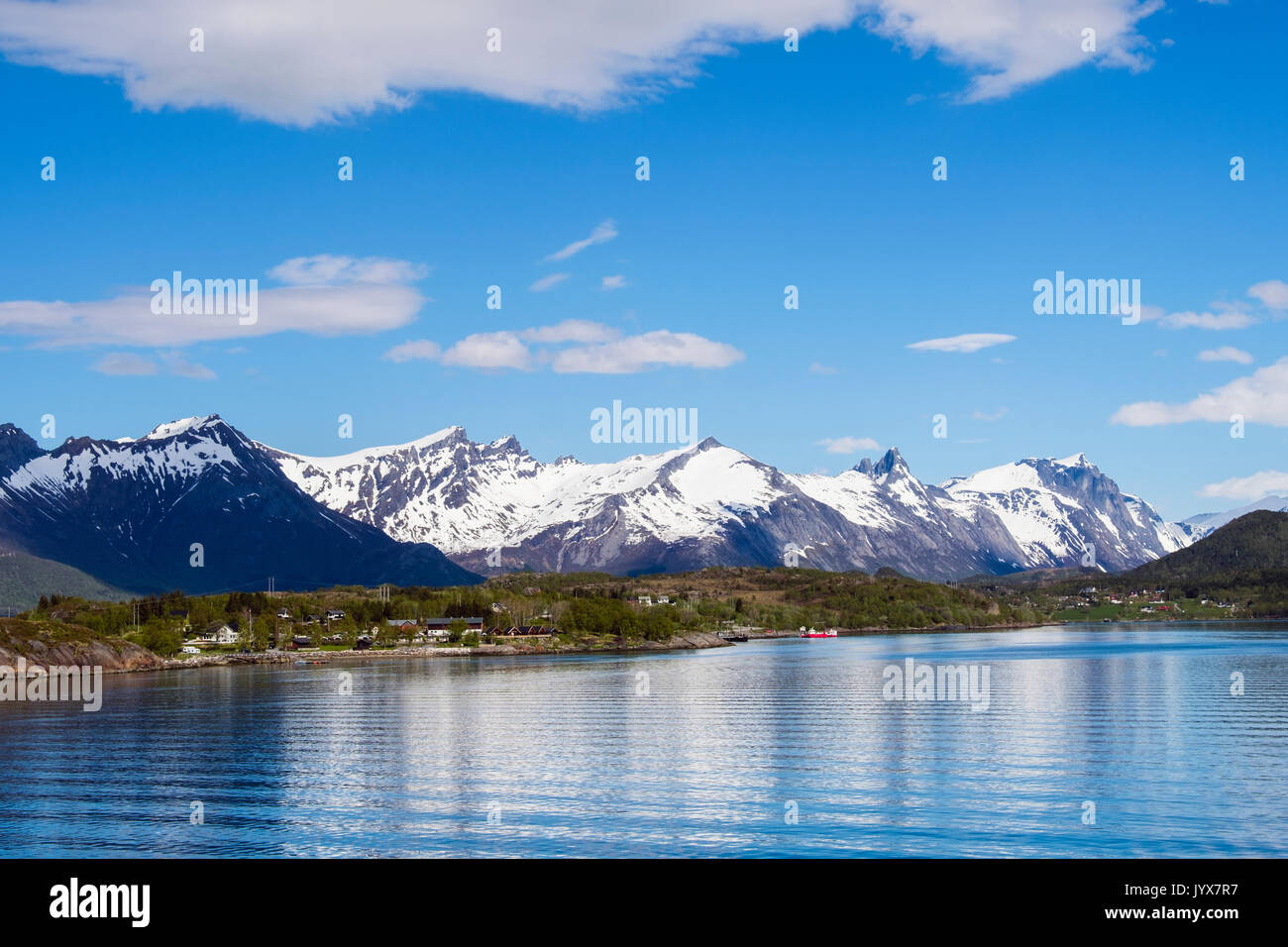 Offshore view to snowcapped mountains and campsite beside Arhaugfjorden fjord on Norwegian north west coast in summer. Furoy, Meløy, Nordland, Norway - Stock Image