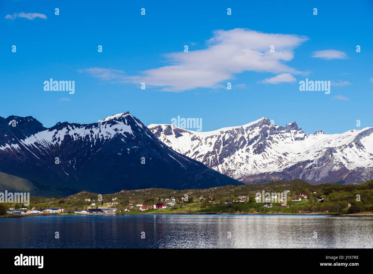 Offshore view to snow-capped mountains and rural kommune beside Arhaugfjorden on Norwegian north west coast in summer. Halsa, Nordland, Norway - Stock Image