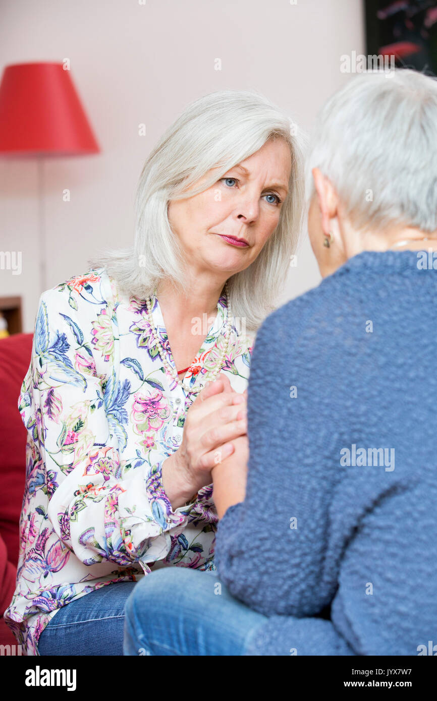 Older woman comforts her friend - Stock Image