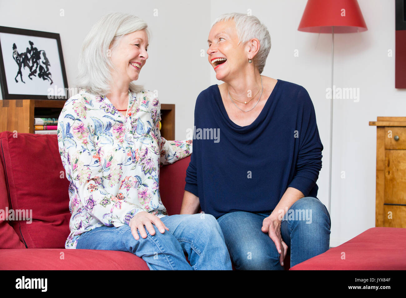 Older friends laughing together - Stock Image