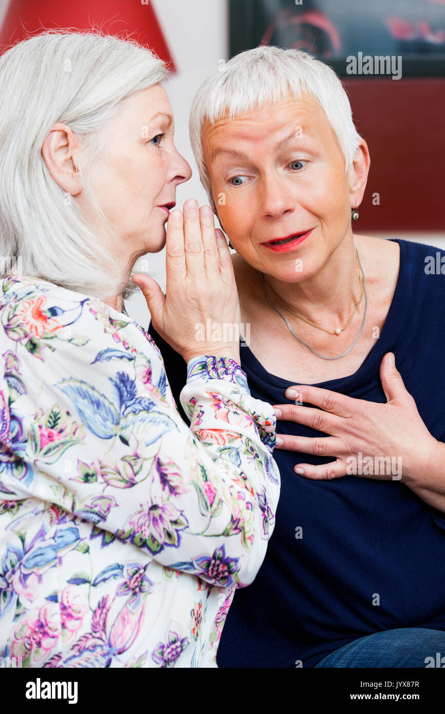 Two older women whispering - Stock Image