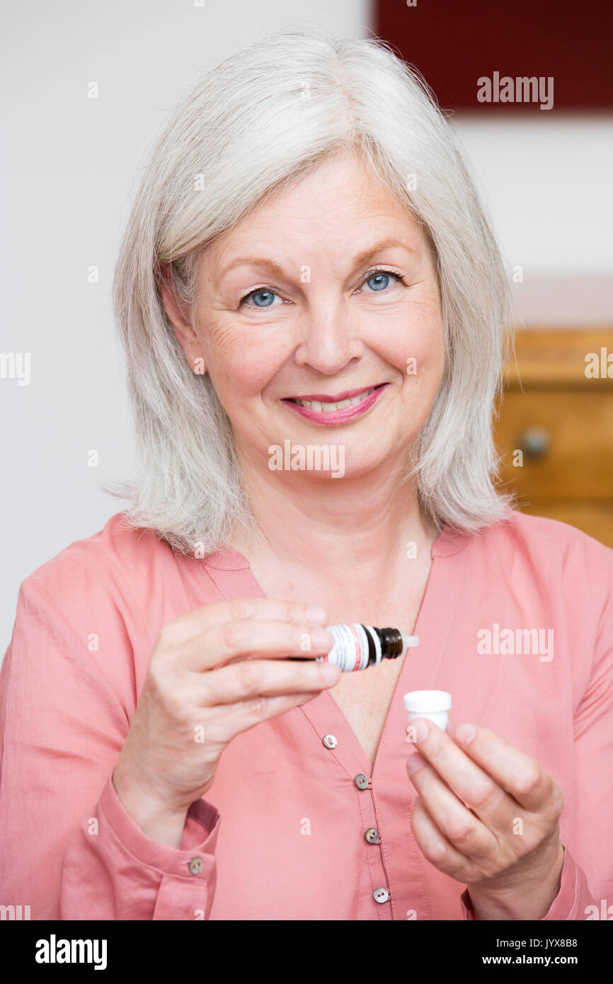 Older woman takes globules - Stock Image