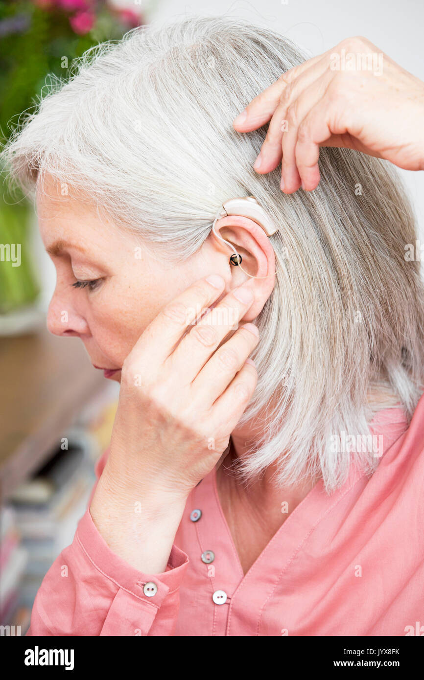 Senior woman with hearing aid device - Stock Image