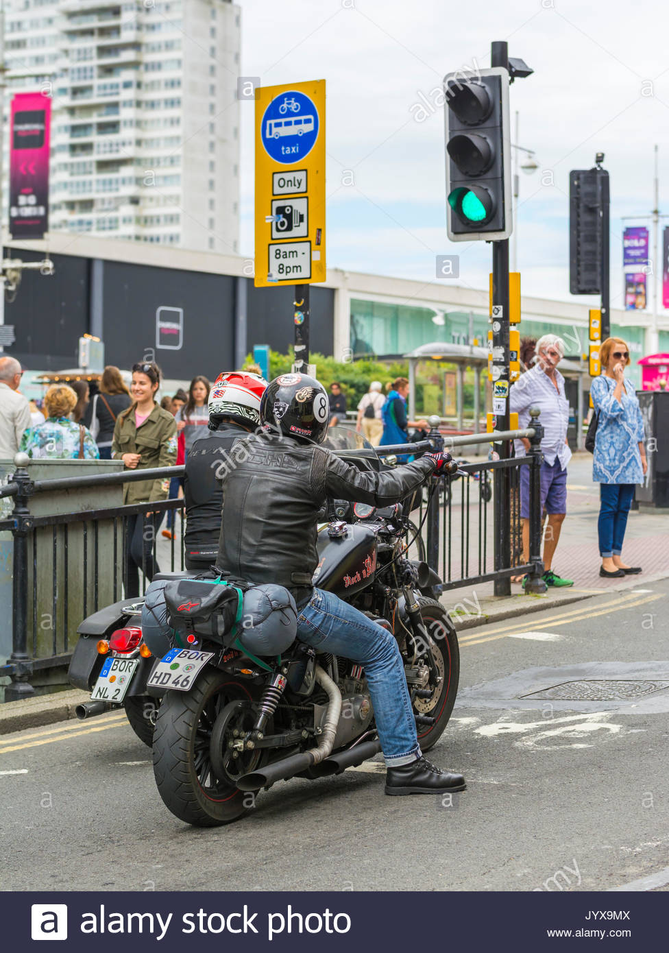 Pair of foreign motorcyclists at traffic lights in the UK. - Stock Image