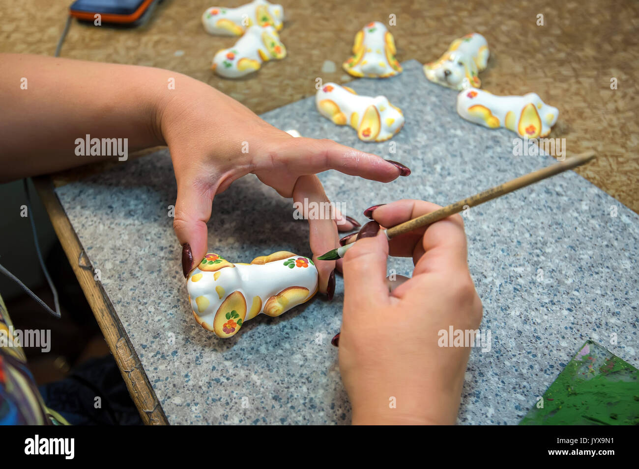 Woman hands paint earthenware figure - Stock Image