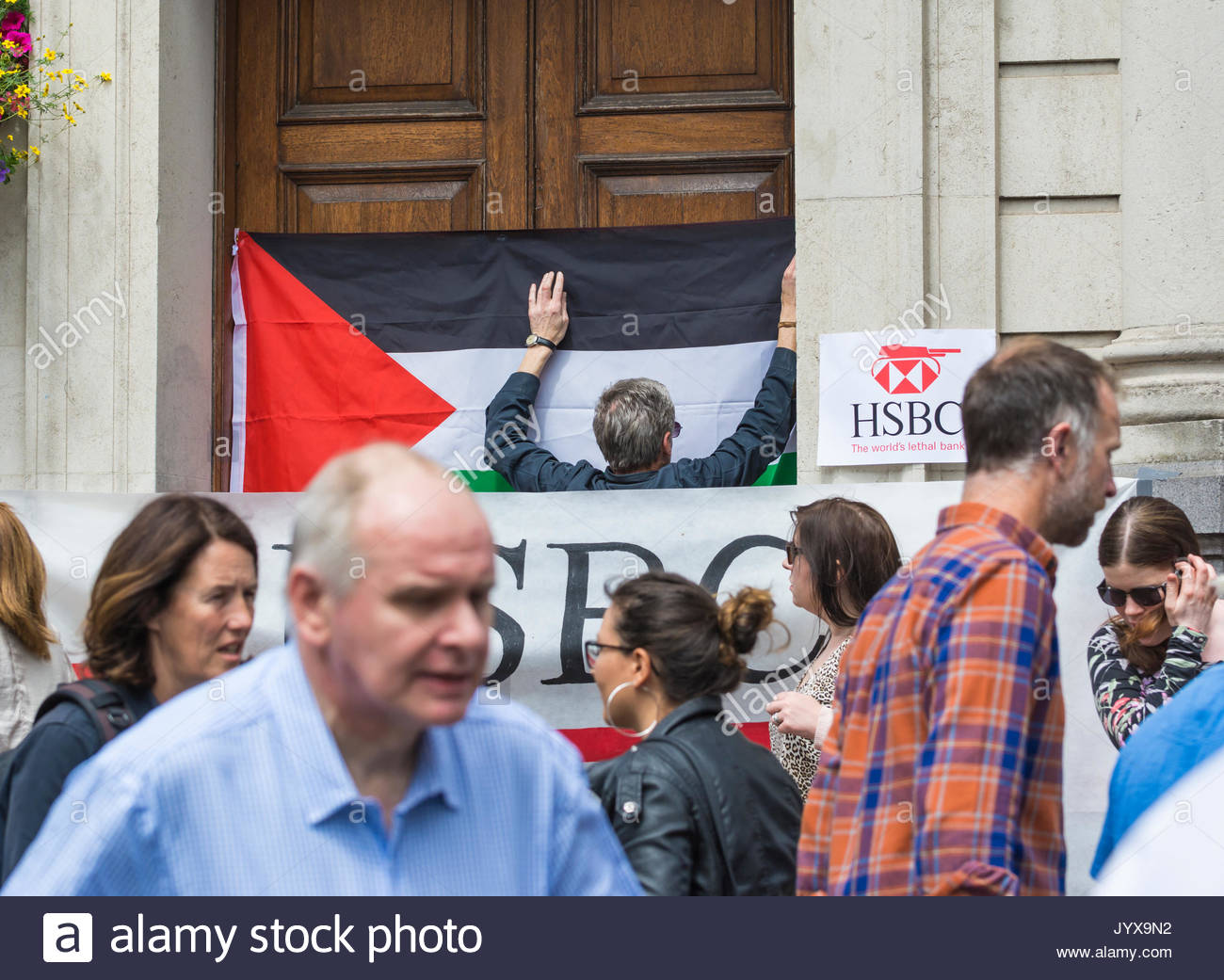 Justice for Palestine protestor hanging a protest sign on the front entrance to the HSBC bank in Brighton, East - Stock Image