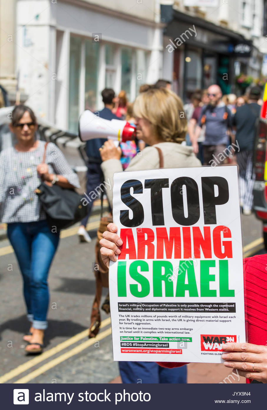 Protestor holding a protest sign up saying 'Stop Arming Israel' outside the HSBC bank in Brighton, East - Stock Image