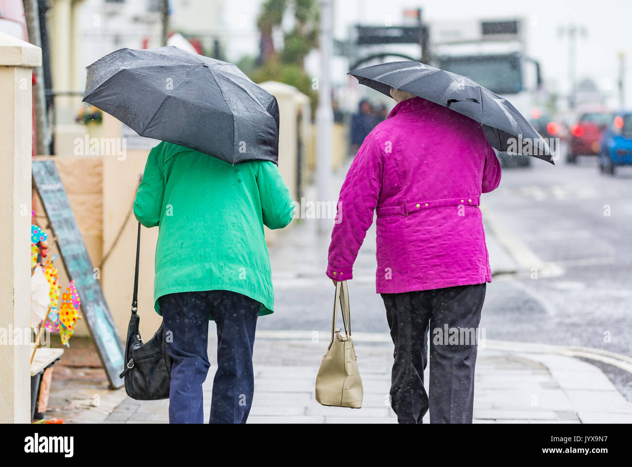 Rear view of people walking in the rain holding umbrellas. - Stock Image