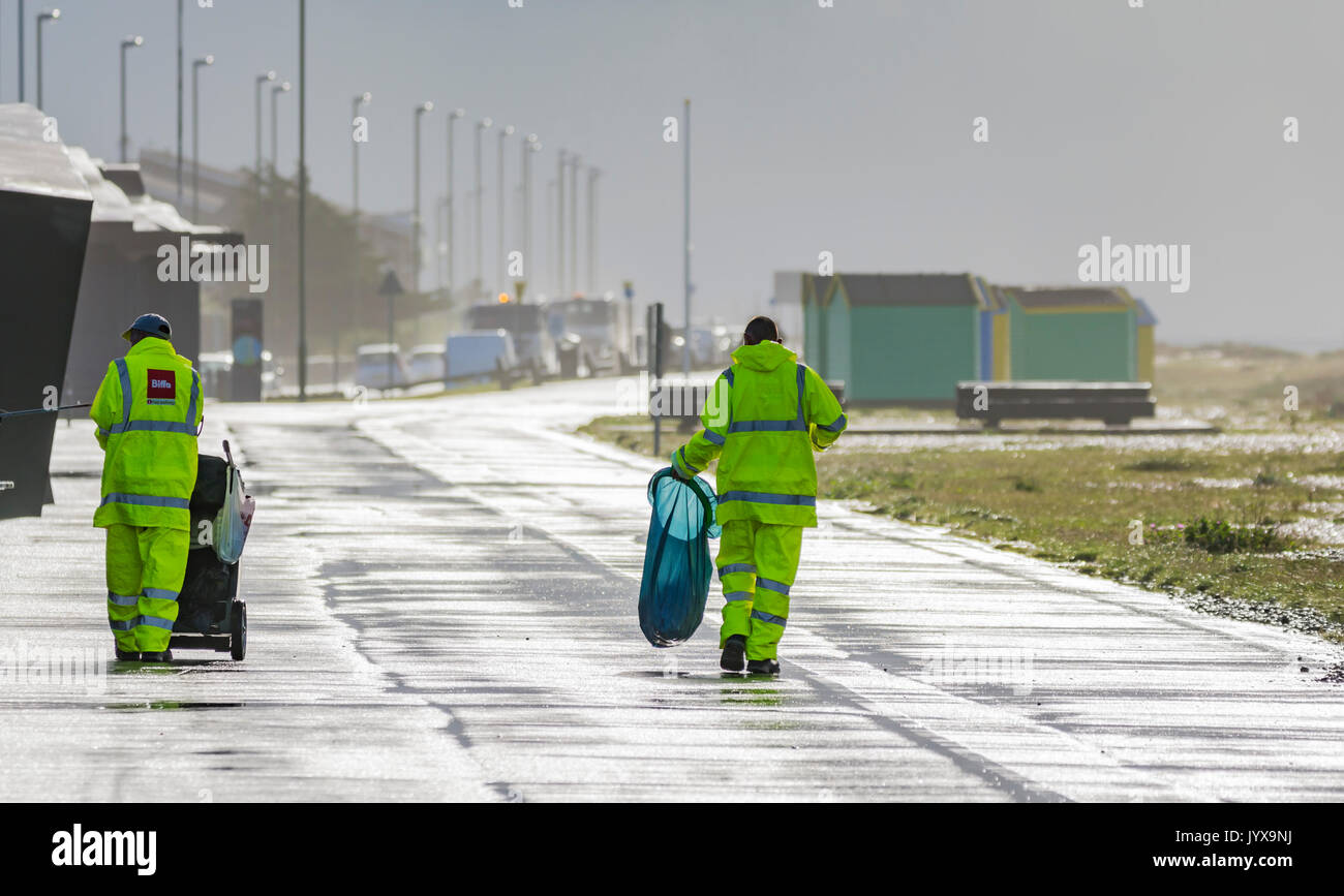 Biffa outdoor cleaners working in the rain with the sun out brielfy reflecting in water on the ground. - Stock Image