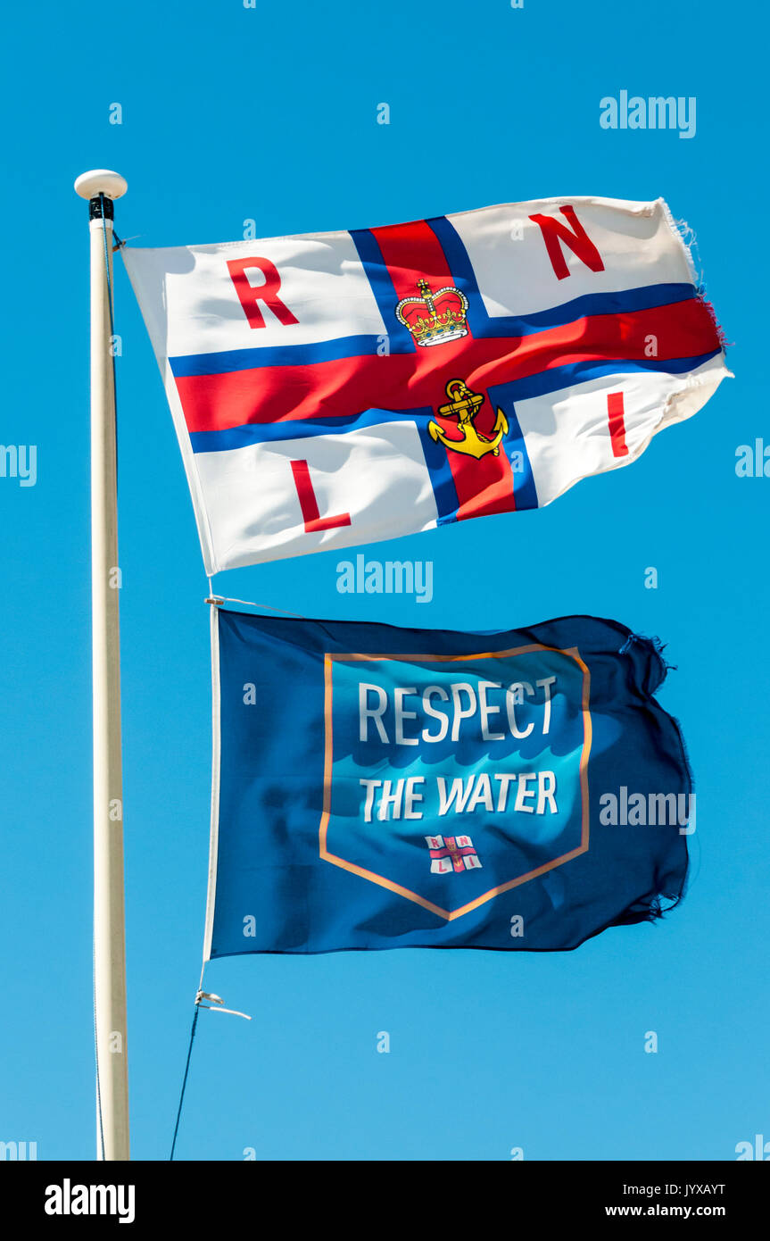 RNLI & Respect the Water flags flying outside the Dungeness lifeboat station. - Stock Image