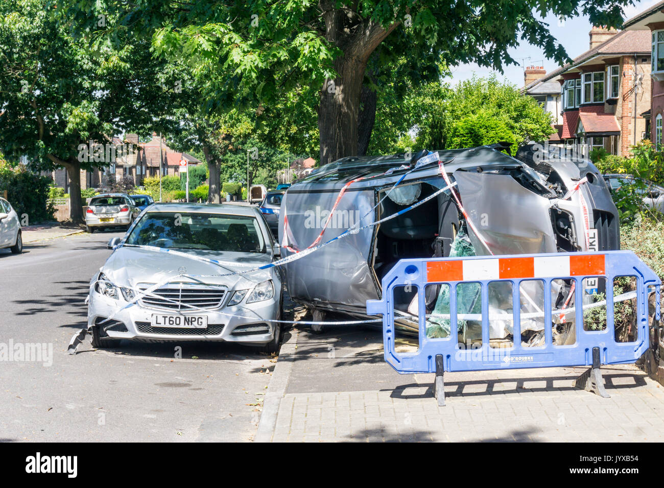 Result of traffic accident in suburban residential road.  Silver Nissan Qashqai Visia car overturned onto side on pavement & covered with police tape. - Stock Image