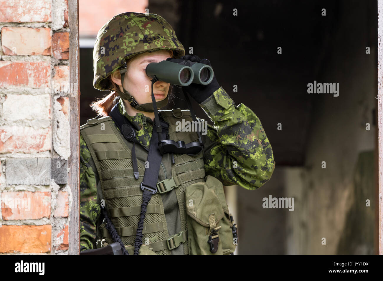 Portrait of armed woman with camouflage. Young female soldier observe with binoculars. Child soldier with gun in war, house ruins background.  Militar - Stock Image