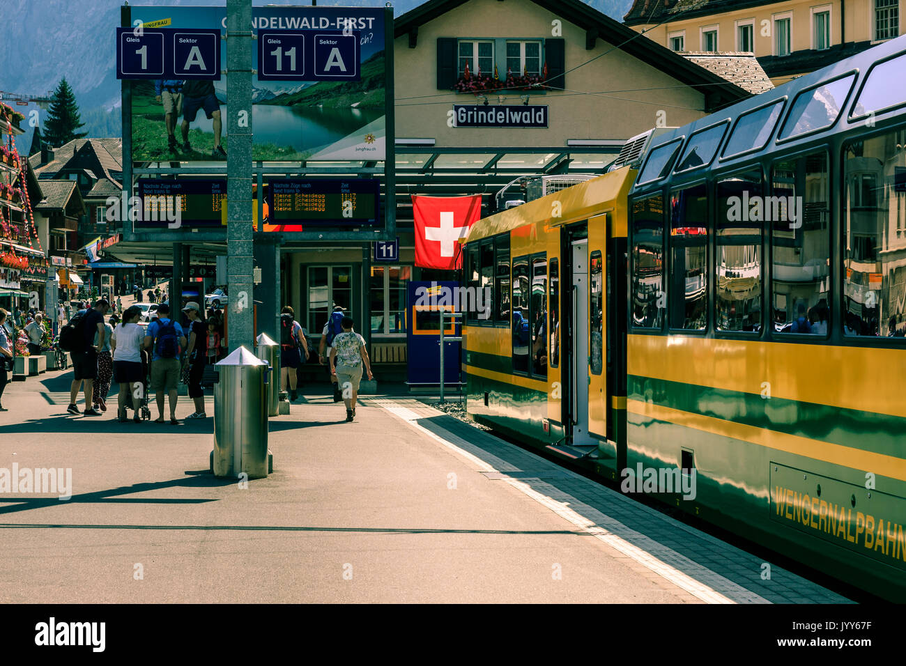 Grindelwald, Bernese Oberland, Switzerland - AUGUST 1, 2017 : Yellow - Green train from the Wengernalpbahn in the Grindelwald railway station - Stock Image