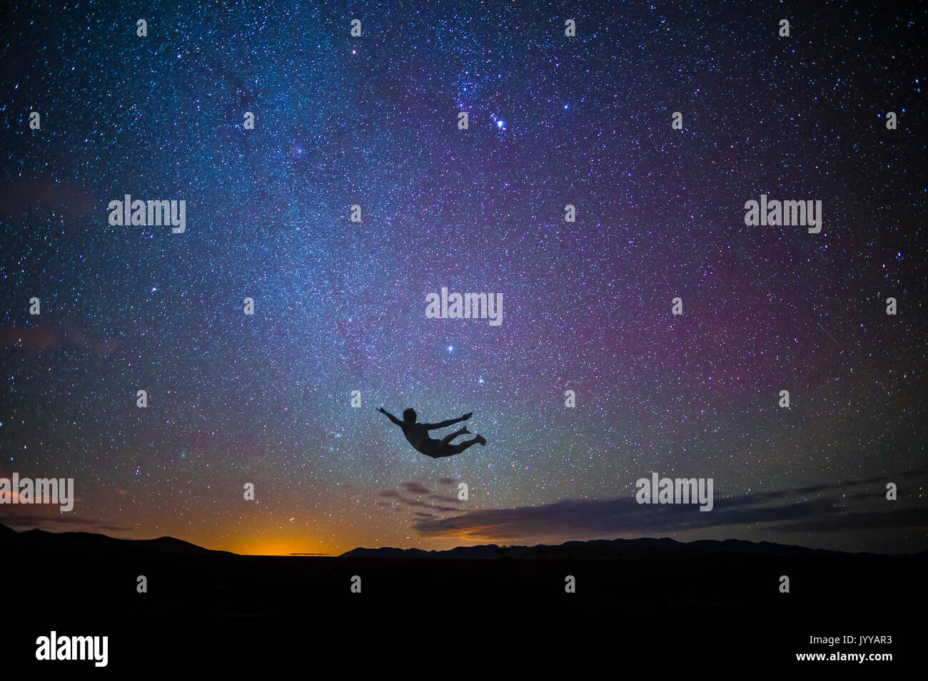 Boy Jumping In Air At Sunset With Stars - Stock Image