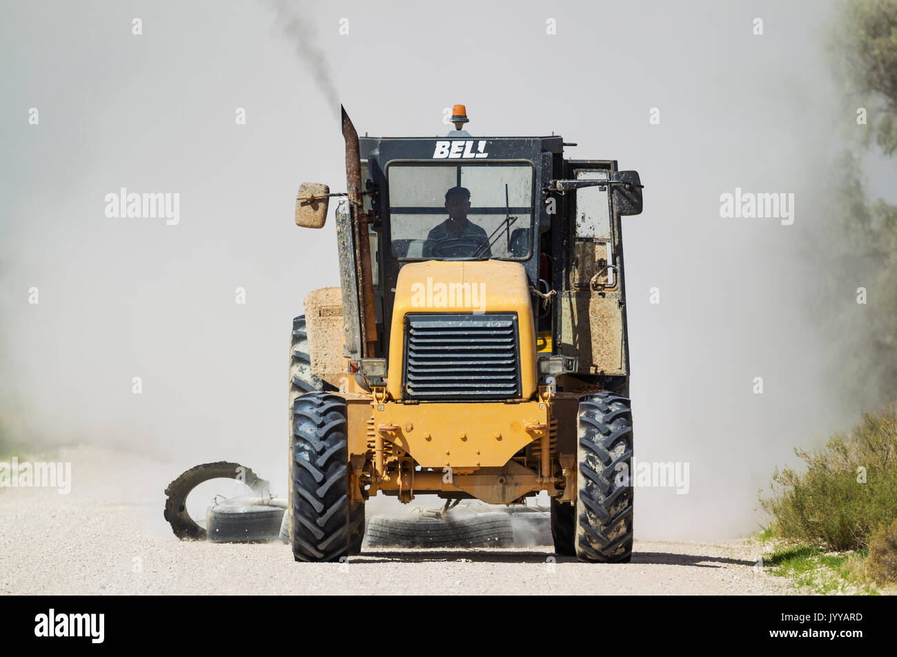 A tractor pulling tyres for grading the parks gravel roads, Kalahari Desert, Kgalagadi Transfrontier Park, South Africa - Stock Image