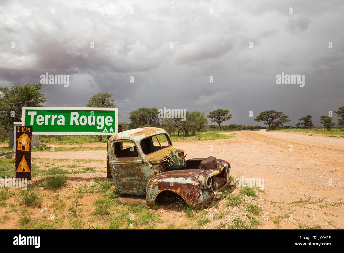 Car wreck at the entrance gate of Terra Rouge guest farm, rainy season with green vegetation, C 15 gravel road, - Stock Image
