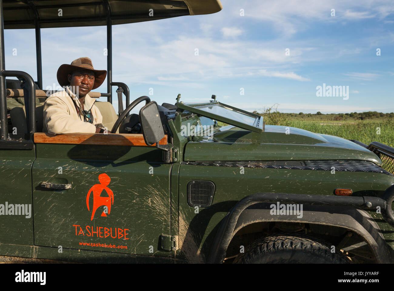 A driver and guide in a safari jeep, Kalahari Desert, Kgalagadi Transfrontier Park, Botswana - Stock Image