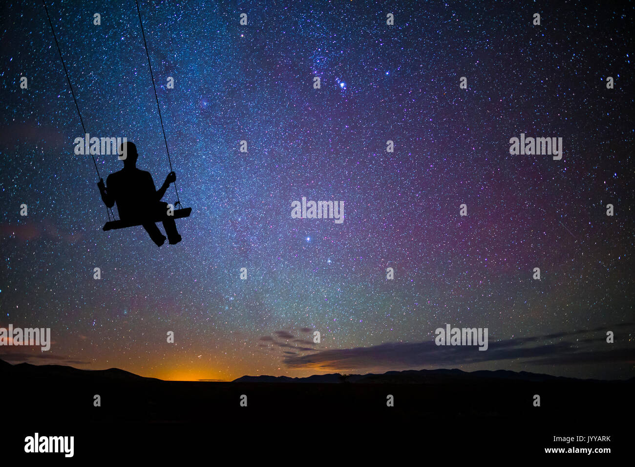 Child On Swing Swinging With The Stars At Night - Stock Image